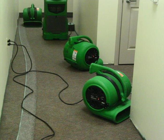 green SERVPRO fans drying wet carpet and walls