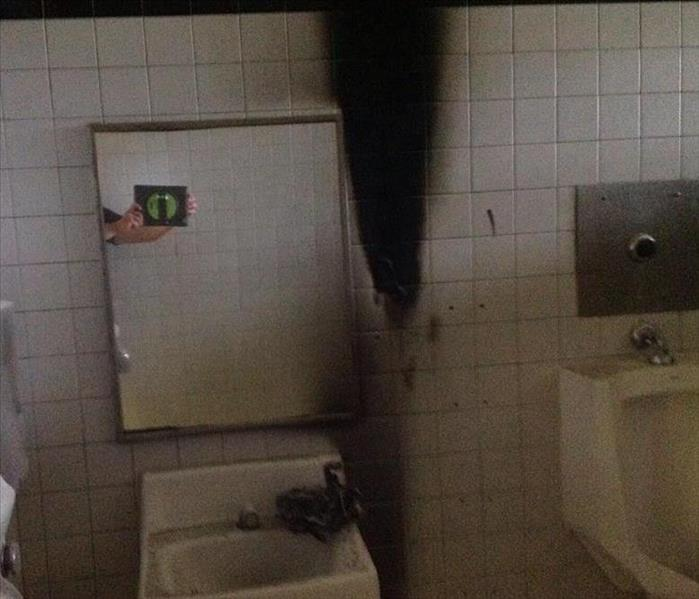fire damaged charred tile wall in bathroom