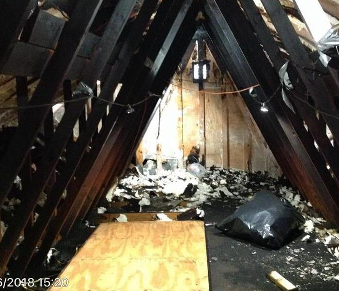 Charred trusses in an attic with fire debris
