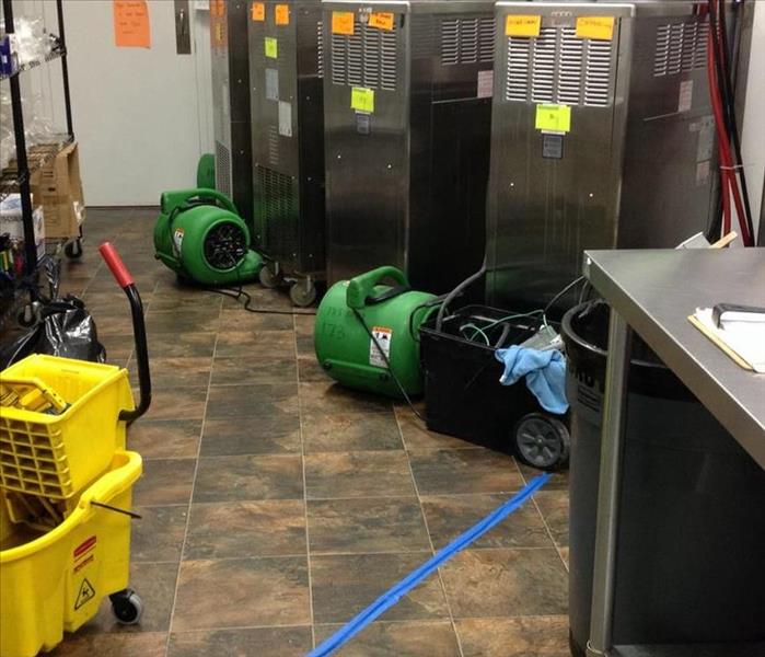 green SERVPRO fans drying tile floor