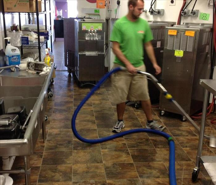 SERVPRO member removing water from tile floor