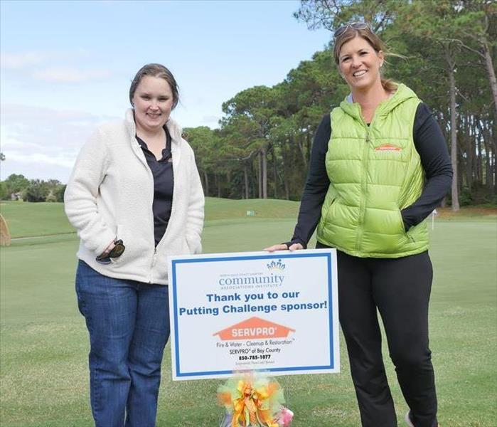 Two Women on a Golf Course with a Small Sign